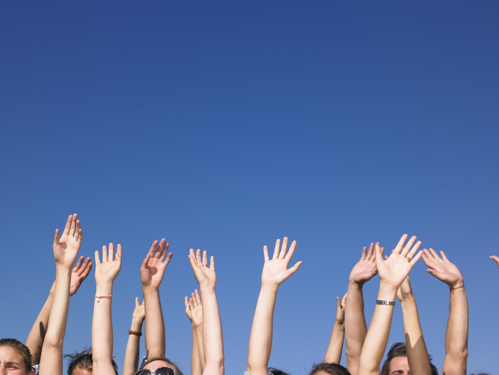 collection of people with their hands in the air